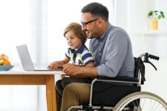 Man in wheelchair looks at laptop computer with his young son