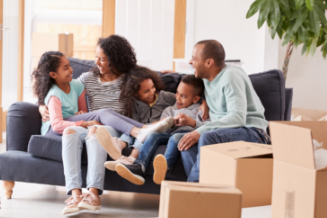 Happy family of 5 sitting on couch surrounded by moving boxes