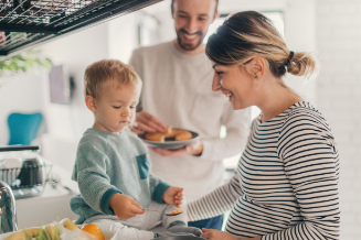 Young couple with toddler cooking breakfast together